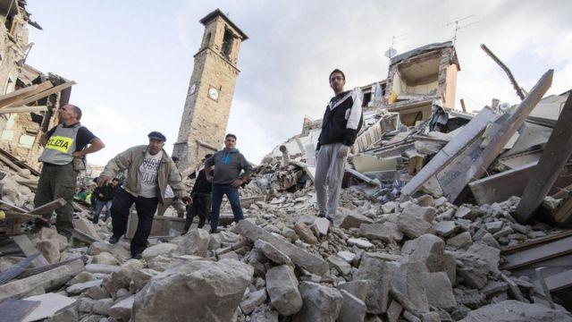 Gente buscando en escombros. Sólo queda una torre levantada.