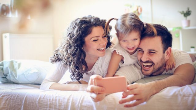 Padres con niña y celular.