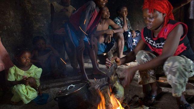Una mujer sostiene sobre el fuego la carcasa de un mono