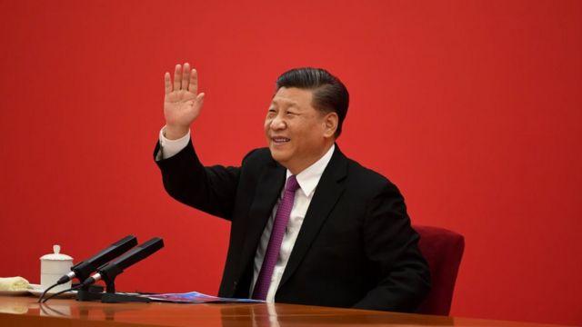 Xi Jinping acenando diante de fundo vermelho