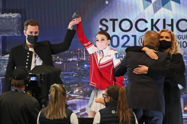 Figure skater Anna Shcherbakova (C) of Russia, the gold winner, celebrates her victory with her coaches Daniil Gleikhengauz (L), Eteri Tutberidze (R), and Sergei Dudakov (2nd R)