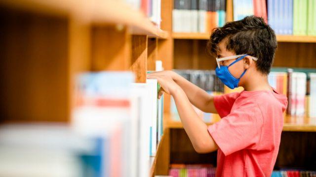 Menino usando máscara mexe em livros na estante