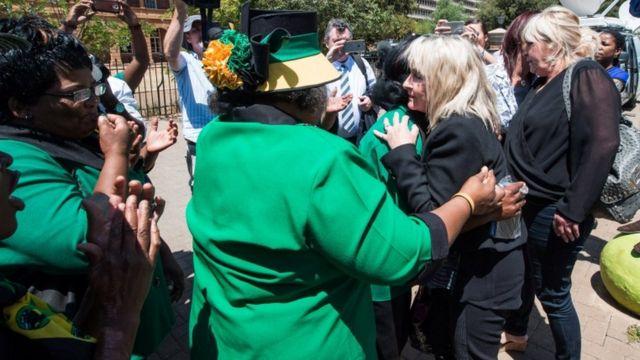 与党ANCの女性たちに抱きしめられるジューンさん