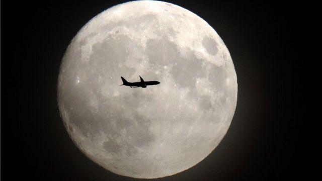 Luna llena con un avión.