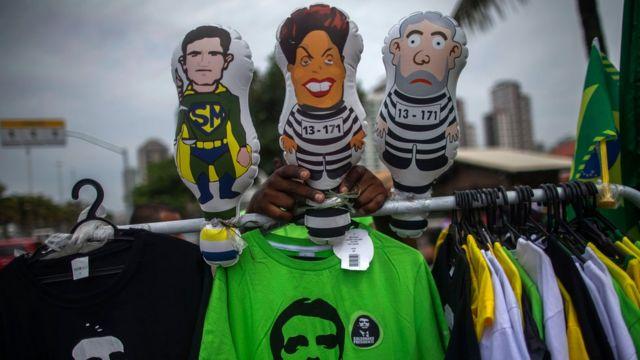 Camisetas de Bolsonaro e bonecos infláveis de um 'super-heroi' Sergio Moro, e de Dilma e Lula presidiários, em frente ao condomínio onde vive o futuro presidente, no Rio