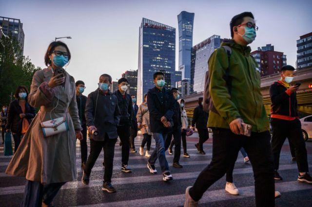 Trabalhadores cruzam uma rua de Pequim durante a hora do rush