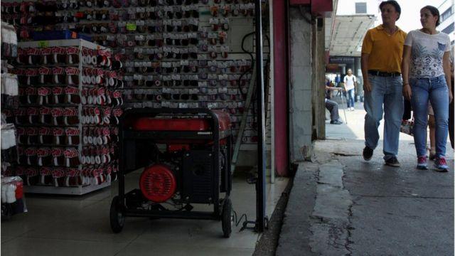 Una pareja pasa frente a una tienda con generador durante un apagón en San Cristóbal, Venezuela.