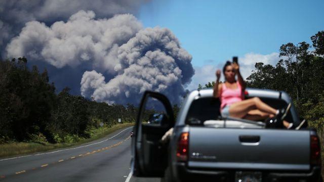 Una mujer se toma una selfie con una nube de humo del volcán Kilauea como fondo.