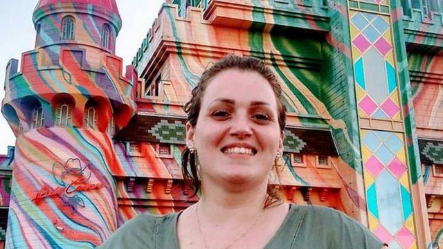Erika sorri para foto em frente a construção turística, durante viagem