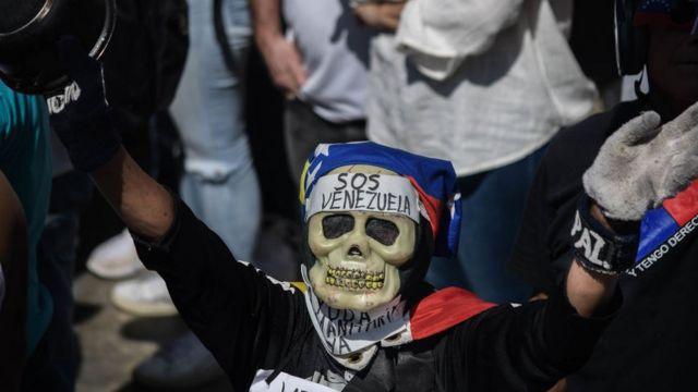 """Venezolano con una máscara de una calavera y un cártel que dice """"SOS Venezuela""""."""
