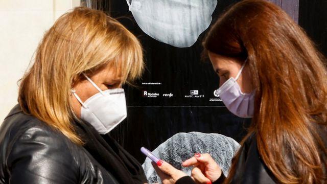 Two women wearing masks