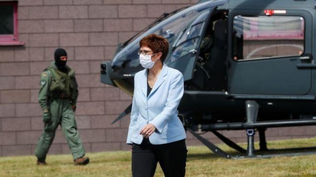 De máscara, a ministra da defesa alemã, Annegret Kramp-Karrenbauer, caminha em pátio, com homem fardado e helicóptero atrás