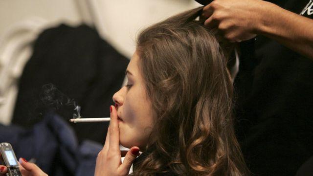 سيدة تدخن في محل لتصفيف الشعر