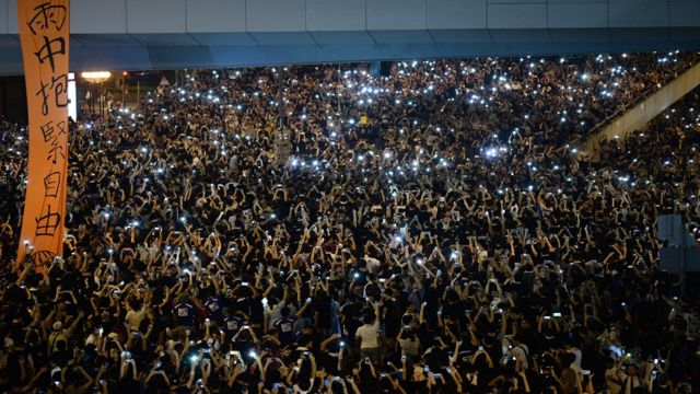 Pro-democracy demonstrators hold up their mobile phones during a protest near the Hong Kong government headquarters on 29 September, 2014