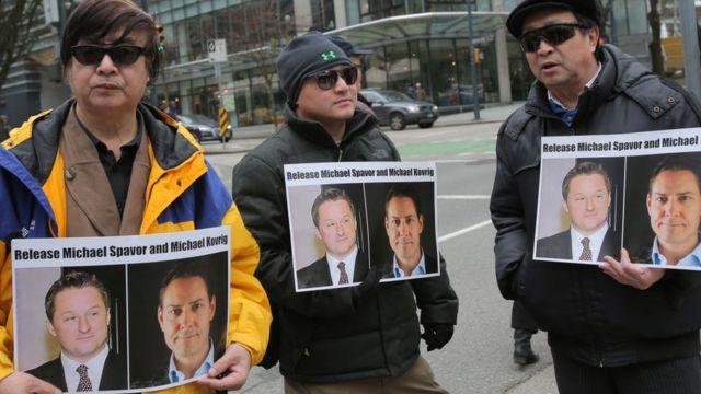 Manifestantes sostienen carteles pidiendo la liberación de Michael Spavor y Michael Kovrig