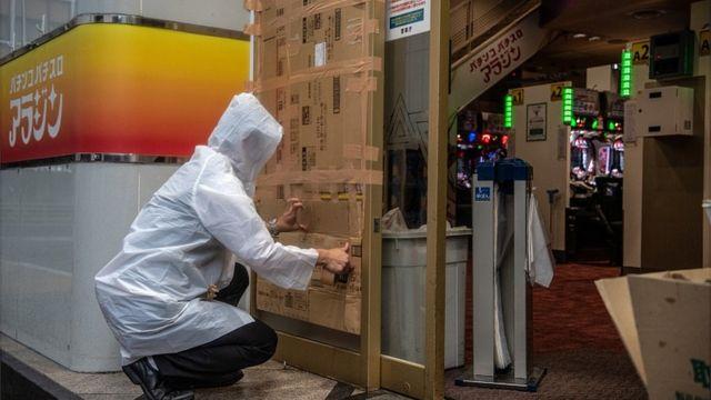 """Мужчина укрепляет дверь в игорный салон в ожидании тайфуна """"Хагибис"""" (Токио, 12 октября 2019 года)"""