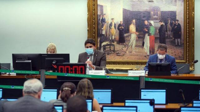 Os deputados Juscelino Filho (DEM - MA) e Cezinha de Madureira (PSD - SP) de máscara sentados diante de mesa de comissão