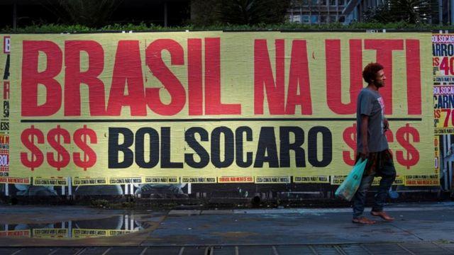 """Homem caminha descalço em frente a uma faixa que diz """"Brasil na UTI, Bolsocaro"""" em São Paulo, Brasil, 8 de março de 2021"""