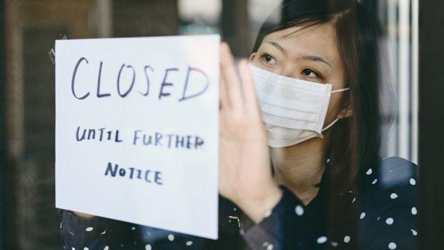 Una mujer con una anuncio de cerrado