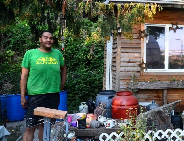Um homem apelidado de Tequila diante da casa em que vive em um acampamento para pessoas sem teto em Portland, nos EUA
