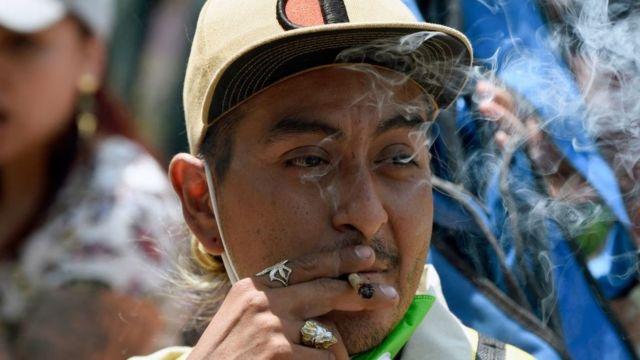 Um homem fuma um baseado durante uma manifestação exigindo a legalização da maconha para uso recreativo, em frente ao Senado na Cidade do México