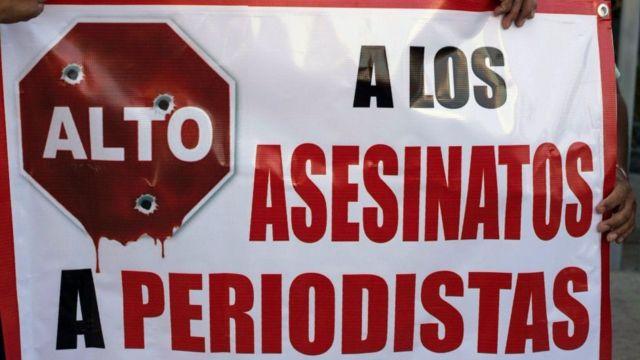 """Cartel que dice: """"alto a los asesinatos a periodistas""""."""