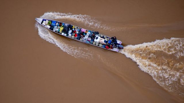 Imagem aérea mostra barco carregado de barris e pessoas em água marrom do rio