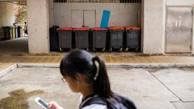 Una joven pasa ante los contenedores de basura a las afueras de la vivienda del hombre contagiado.