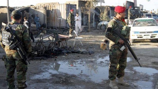 空港襲撃で焼かれた店舗の前を警備するアフガン国軍兵士(9日)
