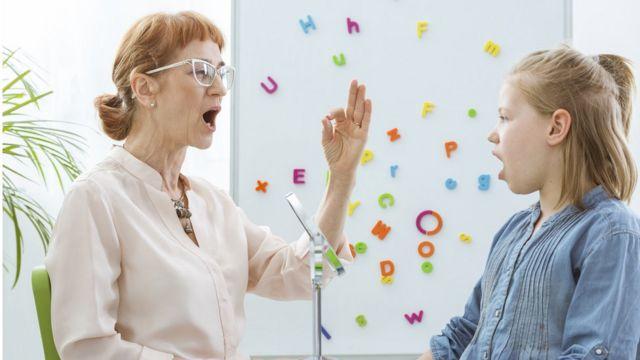 Mujer madura y niña practican la fonética.