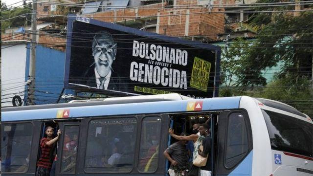 Os passageiros viajam em um ônibus público lotado, passando por uma painel contra o presidente Jair Bolsonaro