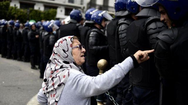 Пожилая женщина разговаривает с полицейскими алжирских спецподразделений во время недавних протестов