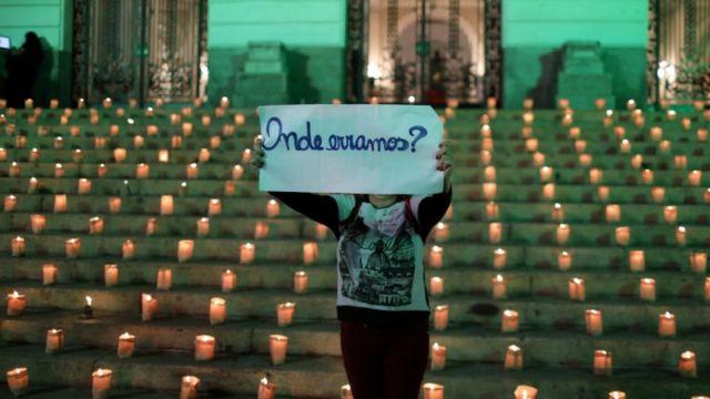 Em frente a escadaria com velas, manifestante segura cartaz que diz: 'Onde erramos?'