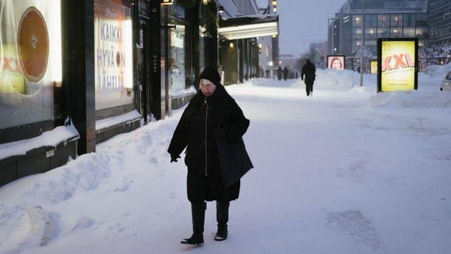 Woman walking on a snow covered street in Helsinki