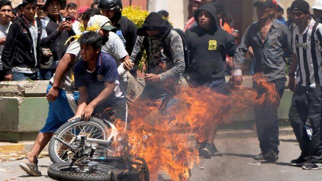 Una motocicleta se quema rodeada por manifestantes.