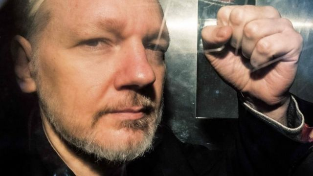 WikiLeaks founder Julian Assange gestures from the window of a prison van as he is driven into Southwark Crown Court in London on 1 May 2019