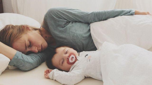 Una mujer duerme en la misma cama con un bebé.
