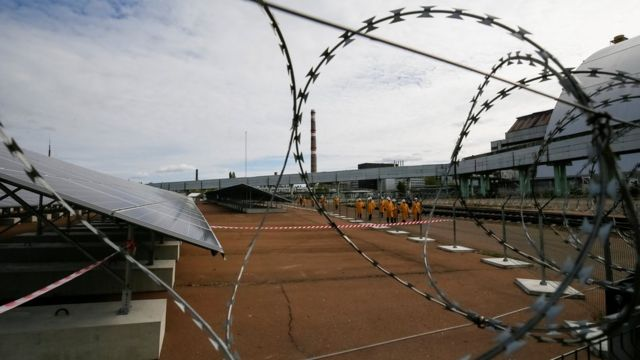 Солнечные панели на фоне колючей проволоки перед новым саркофагом, построенным над остатками поврежденного четвертого блока реакторов ЧАЭС