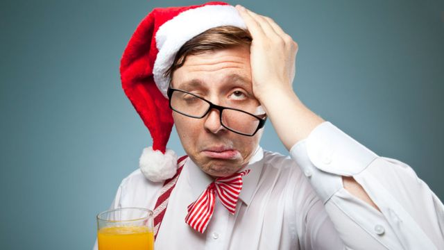 Hombre con resaca usando un sombrero de Papá Noel.
