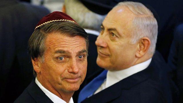 Jair Bolsonaro e Benjamin Netanyahu olham para direções opostas, com sorrisos tímidos, durante evento no Rio de Janeiro