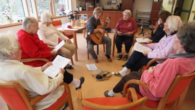 Des personnes dans un foyer de soins résidentiels pour personnes atteintes de la maladie d'Alzheimer et de démence chantent en compagnie d'un thérapeute.