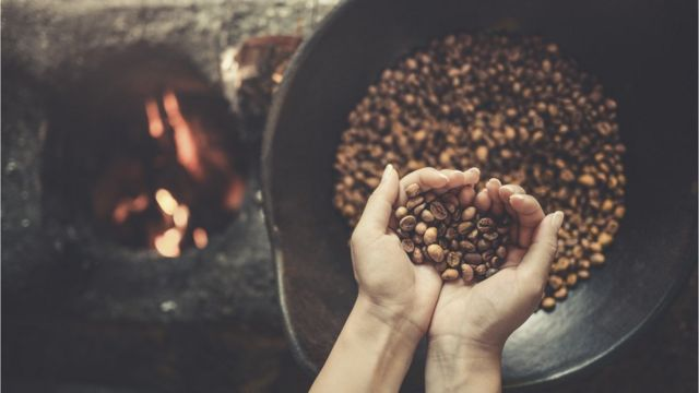 Female hands holding freshly roasted coffee beans above a bowl next to a fire.