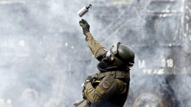 Un militar lanza un cartucho de gas lacrimógeno