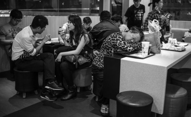 A homeless woman asleep among awake regular customers in the restaurant