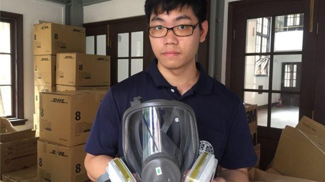 Alex Ko holding a gas mask in a church storage room