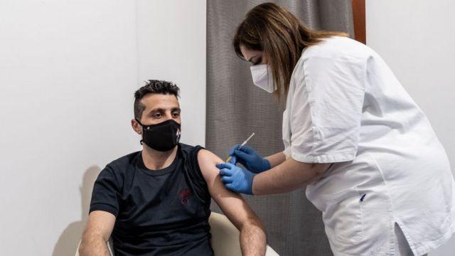 Una enfermera vacuna a un hombre joven en Italia.