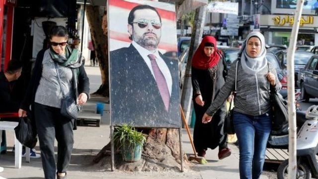Mujeres pasan al lado de una foto de Saad Hariri en Beirut.