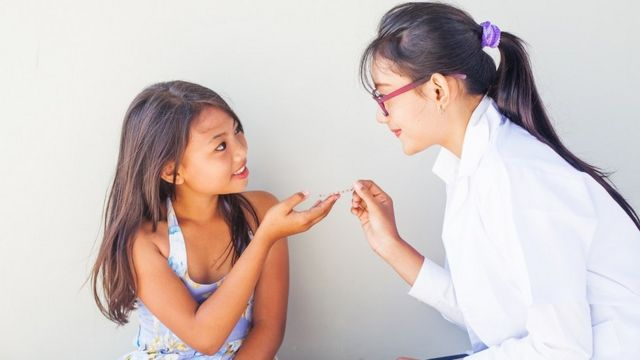 A doctor gives medicine to a child
