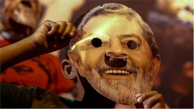 Militante com máscara de papel representando o rosto de Lula