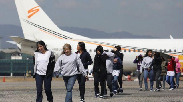 Mujeres deportadas bajando de un avión.